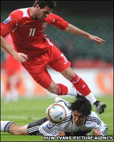 Germany defender Serdar Tasci brings down Joe Ledley