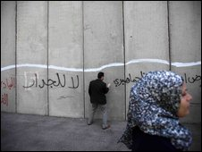 A Palestinian sprays graffiti on a section of Israel's barrier in Bethlehem, 30 March
