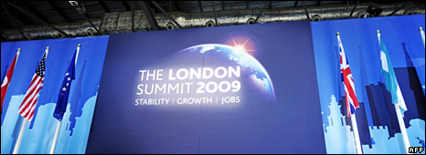 People walk past the G20 logo in the main press centre of the ExCel Centre in London (1 April 2009)