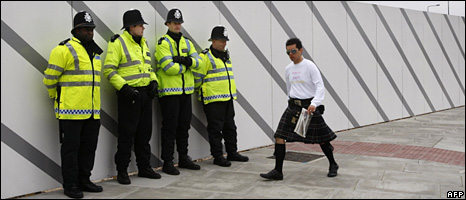 A man in a kilt walks past police near the Excel Centre (20 April 2009)