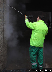 A contractor cleaning graffiti
