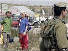 Two teenage Jewish settlers watch as Israeli forces block a road leading to Bat Ayin