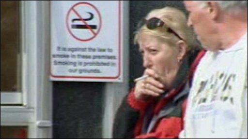 Lady smokes a cigarette next to a no smoking sign