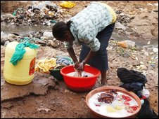 A woman does her washing in a Kenya slum