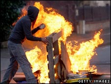 A protestor near a burning barricade in Strasbourg