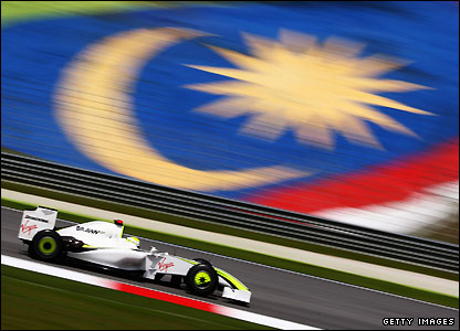 Jenson Button zooms past a Malaysian flag