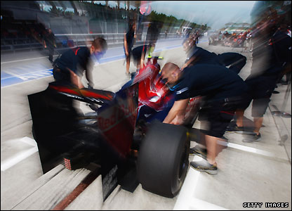The Torro Rosso mechanics go to work on Sebastien Buemi's car