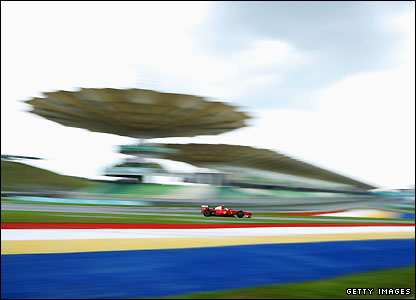 Kimi Raikonen's Ferrari stands out against the famous Sepang grandstand