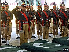 Pakistani police pay tribute at the coffins of policemen during a funeral in Lahore (Photo: AAMIR QURESHI/AFP/Getty Images)