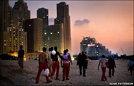 Dubai workers on beach near high rise buildings at dawn