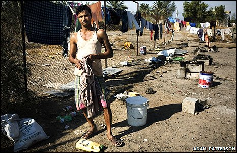 Dubai worker stands in front of washing and cooking facilities