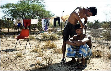 Dubai worker having hair cut by fellow worker