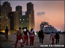 Migrant workers walk past luxury developments in Dubai
