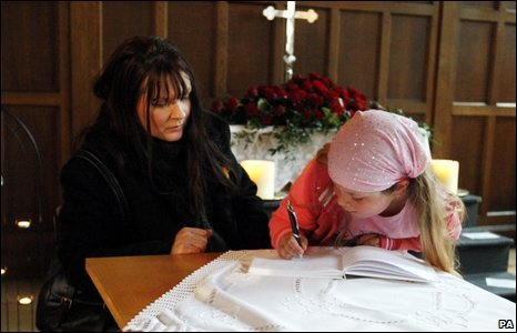 A woman and child signing the book of condolence