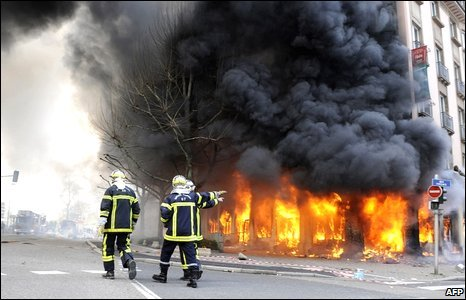 Firemen walk past a burning hotel during an anti-Nato demonstration in Strasbourg, France, 4 April 2009