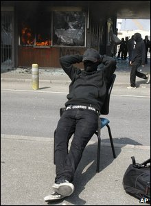 An anti-Nato activist sits on a chair in front of the burning former customs station at the French-German border in Strasbourg, France, 4 April 2009