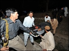 Pakistani security personnel in Islamabad evacuate a wounded colleague by stretcher after the blast on 4 April