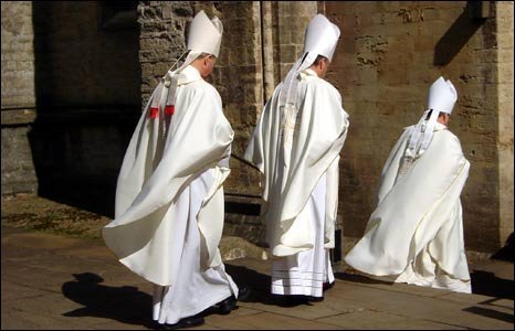 Image shows three members of the clergy in white robes progressing down the steps of the Cathedral