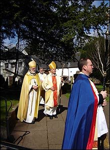 Image shows the Archbishops processing towards the camera and the door of Llandaff Cathedral.