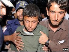 A survivor is helped out of a hospital in Quetta, 4 April