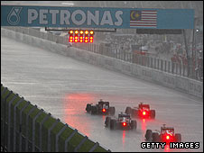 Drivers stop in Sepang as a storm hovers overhead