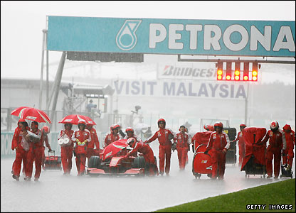 The Ferrari team try and shelter one of their cars from the rain