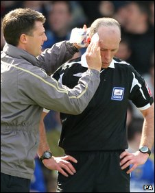 Referee Mike Dean receives treatment after being hit by an object thrown from the crowd
