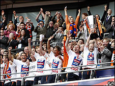 Luton's players show off the trophy