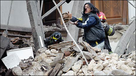 Rescuers work through the rubble in the quake-hit Italian city of L'Aquila on 6/4/09