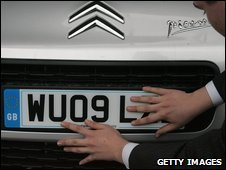 Registration plates being put on a new car