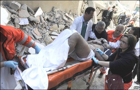 A survivor is removed by rescuers from a damaged building