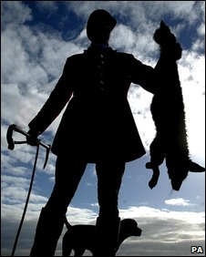 A huntsman holds up a fox after it was shot in the South Durham Hunt