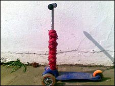 Scooter festooned with red rubber bands