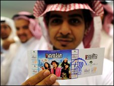 "A Saudi man holds up his entrance ticket to see the Saudi comedy film ""Manahi"" at a theatre in Jeddah"