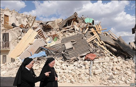 Nuns walk past a destroyed house in the Italian town of Onna after a quake on 7 April, 2009.