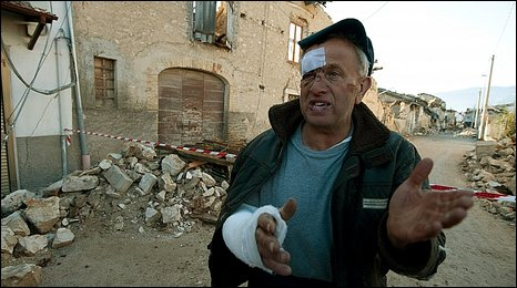 An injured resident of Onna, central Italy, gestures at a barrier into the damaged town.