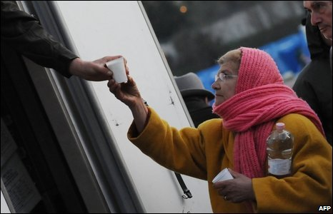 A Civil Protection volunteer distributes milk to people, 7 April