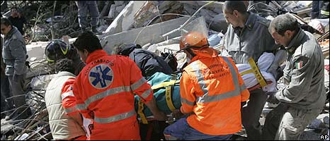 Rescuers carrying a victim from the rubble in L'Aquila