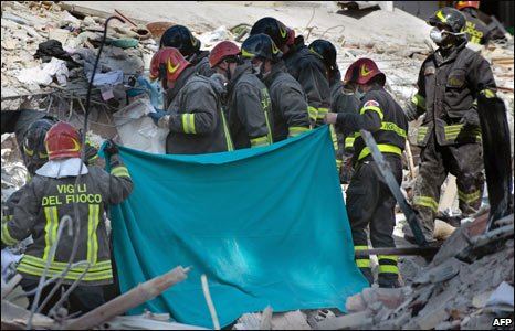 Firefighters hold up a blanket as they retrieve a body from rubble in L'Aquila, Italy