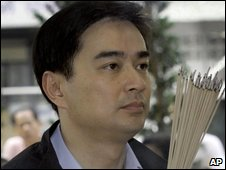 Abhisit Vejjajiva holds incense sticks during a religious ceremony to mark the 63rd anniversary of the Democrat Party
