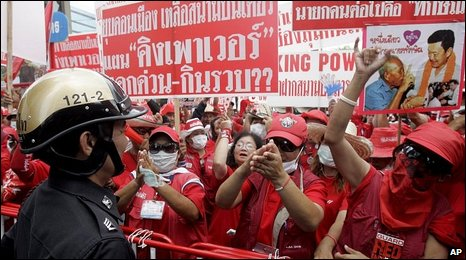 A Thai police officer talks with anti-government protesters and supporters of deposed Prime Minister Thaksin Shinawatra, April 2009