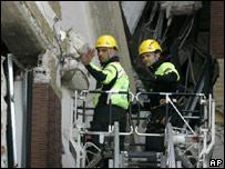 Спасатели у разрушенного землетрясением дома