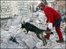A member of a Spanish rescue team and a dog search through rubble in L'Aquila, 8 April