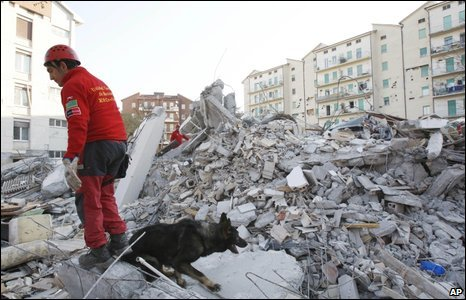 A Spanish rescue worker and his dog search rubble in L'Aquila, 8 April