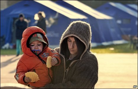 A woman holds her child in a tent camp of L'Aquila