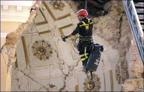 Firefighter Roberto Contu hangs from a line to inspect the damage inside the damaged dome of the church of Santa Maria del Suffragio in L'Aquila