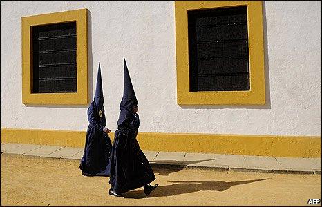 Penitents walk through Seville, Spain