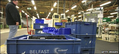 former Visteon employee stands over crates containing components for Ford vehicles at the Visteon factory in Belfast