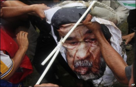Shia protesters pull apart a poster of Saddam Hussein