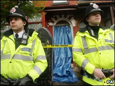 Police stand  outside an address in North Manchester following terror raids in the city